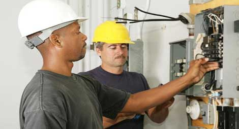 Electrical contractors at work on electrical panel